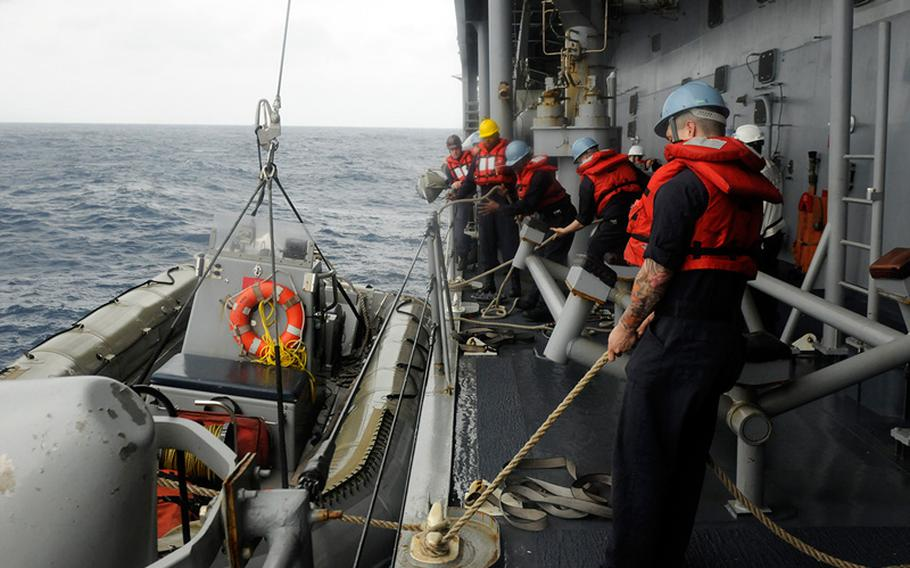 Sailors attached to the U.S. 7th Fleet flagship USS Blue Ridge lower an inflatable boat that will be used to rescue five stranded Philippine fishermen. Blue Ridge is currently on patrol in the Indo-Asian Pacific region.