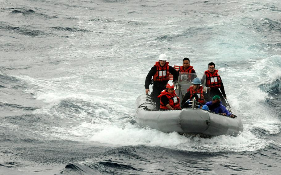 U.S. sailors head to a boat carrying stranded Philippine fishermen. The sailors are attached to the U.S. 7th Fleet flagship USS Blue Ridge.