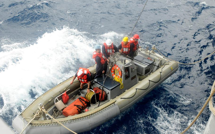 Sailors from the U.S. 7th Fleet flagship USS Blue Ridge prepare to check out a boat flying an orange flag -- an international symbol of distress. The effort resulted in the rescue of five Philippine fishermen.