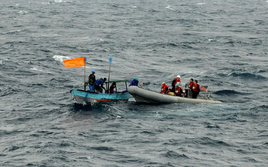 An orange flag, signaling distress, waves from a boat carrying stranded Philippine fishermen on Wednesday, March 25, 2015. Sailors attached to the U.S. 7th Fleet flagship USS Blue Ridge rescued the five fishermen, whose boat had suffered a mechanical breakdown.