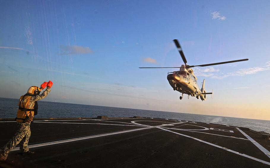 A Dolphin Z-9 helicopter from China's Navy missile frigate CNS Yulin flies off the deck of Singapore's Navy missile frigate RSS Intrepid May 25, 2015, during Exercise Maritime Cooperation 2015 in the South China Sea near Singapore.