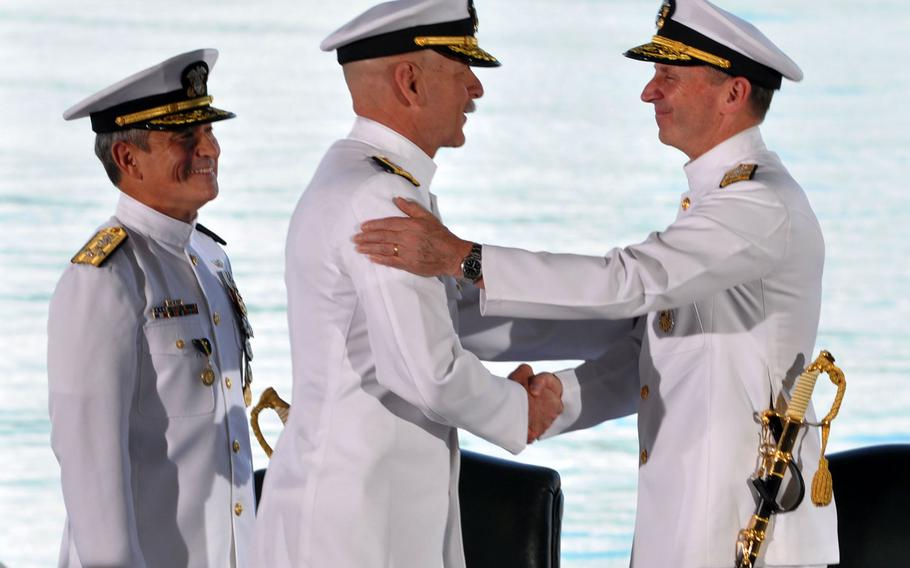 Adm. Jonathan W. Greenert, right, chief of naval operations, shakes the hand of Adm. Scott H. Swift, who assumed command of the U.S. Pacific Fleet during a ceremony at Joint Base Pearl Harbor-Hickam, Hawaii, on Wednesday, May 27, 2015. Adm. Harry B. Harris Jr., who watches from left, assumed command of U.S. Pacific Command at the same ceremony.