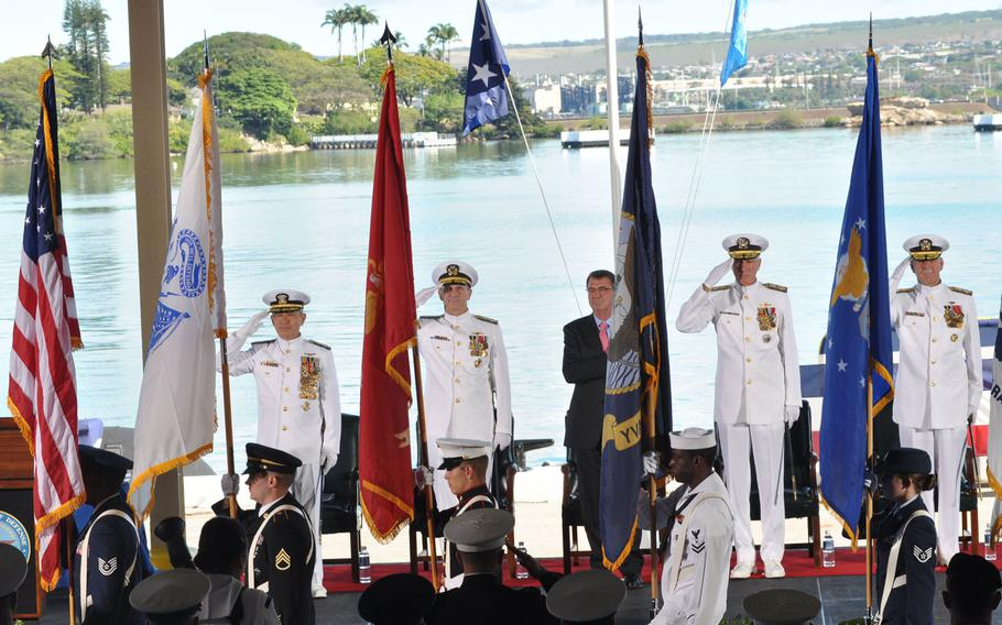 Defense and military officials stand for the national anthem during a change-of-command ceremony Wednesday, May 27, 2015, at Joint Base Pearl Harbor-Hickam, Hawaii. From left are incoming U.S. Pacific commander Adm. Harry B. Harris, Jr.,; Adm. Jonathan W. Greenert, chief of naval operations; Ash Carter, secretary of defense; Samuel J. Locklear, III, retiring PACOM commander; and Adm. Scott H. Swift, incoming commander of U.S. Pacific Fleet.