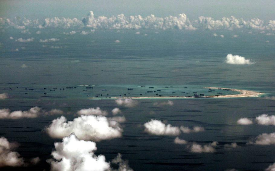 This aerial photo taken through a glass window of a U.S. military plane shows China's alleged ongoing reclamation of Mischief Reef in the Spratly Islands chain in the South China Sea, Monday, May 11, 2015.