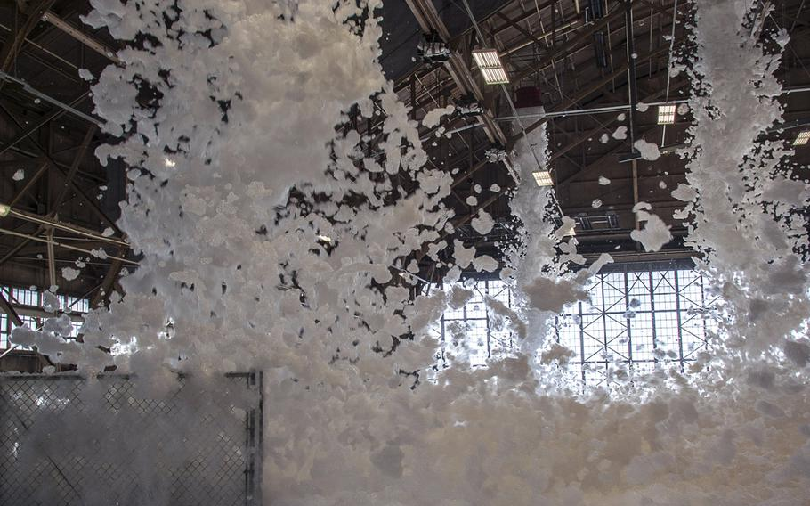 Fire suppression foam engulfs a maintenance hangar as part of a test of high expansion foam discharge in the repair aircraft maintenance hangar April 8, 2015, at Fairchild Air Force Base, Wash.