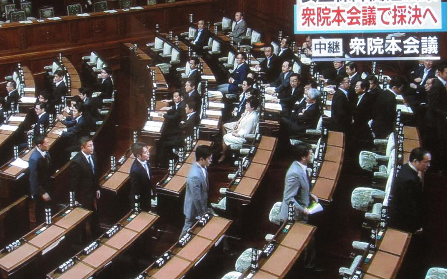 Opposition lawmakers leave the Japan Diet lower house floor on Thursday, ahead of a vote on government-backed bills that would broaden Japan's defense options. The bills passed and will now head to the upper house, where the ruling coalition holds a firm majority.