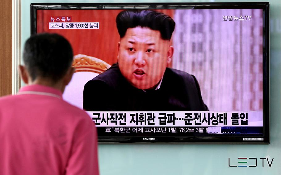 A man looks at a television screen showing an image of Kim Jong Un, leader of North Korea, during a news broadcast on North Korea's exchange of fire with South Korea in August, 2016.
