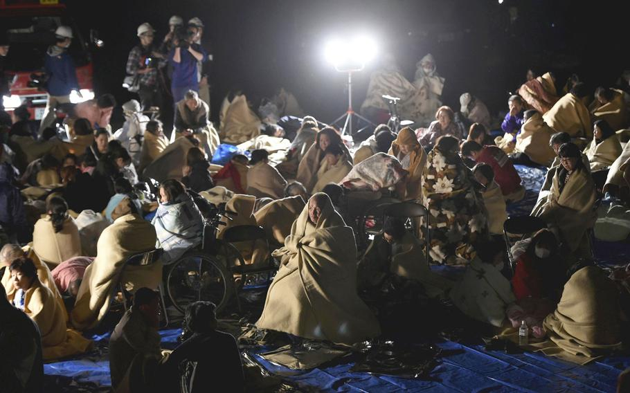 People are seen at a parking lot in Mashiki, Kumamoto Prefecture, Japan, at 1:12 a.m. on Friday after evacuating their homes.