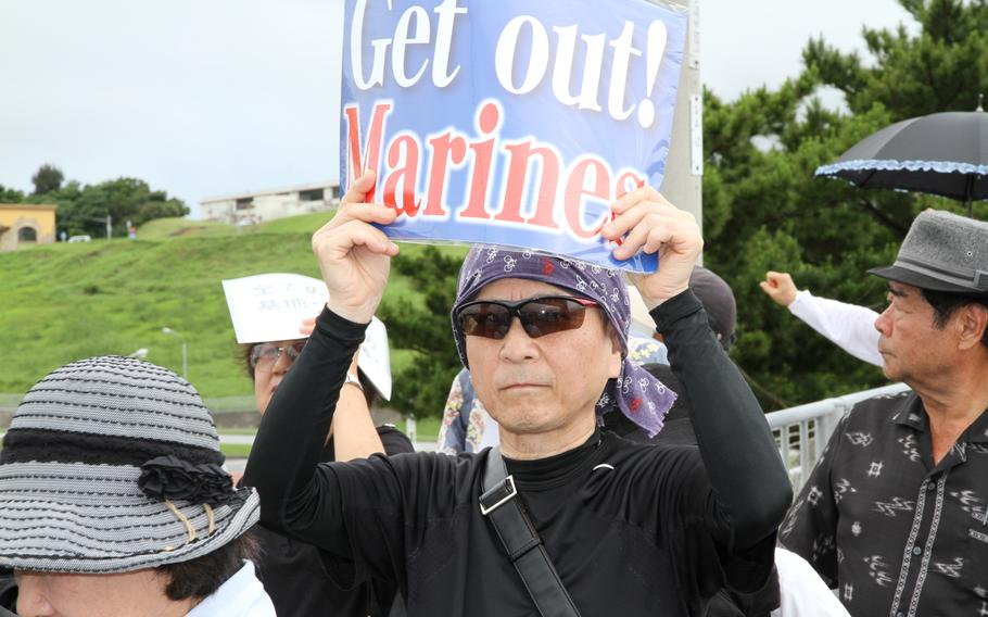 Approximately 2,000 protesters rallied in front of the gate at Marine Corps headquarters on Camp Foster Sunday to protest the U.S. military presence in Okinawa after a former U.S. Marine who worked as a civilian on Kadena Air Base confessed to the brutal slaying of a 20-year-old local woman.