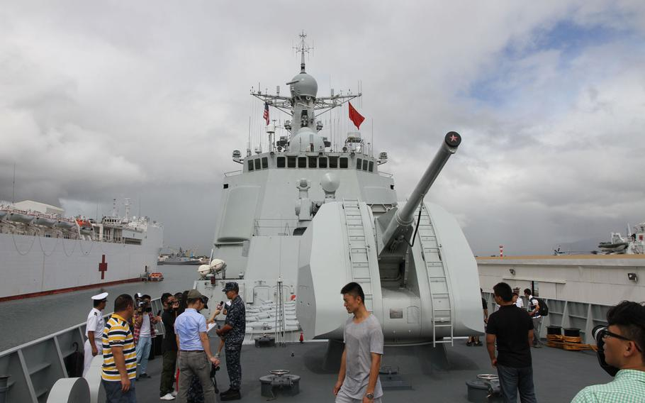 Reporters and other visitors gather to inspect the bow of the Haikou, China's flagship destroyer, during the 2014 Rim of the Pacific exercise in Hawaii.