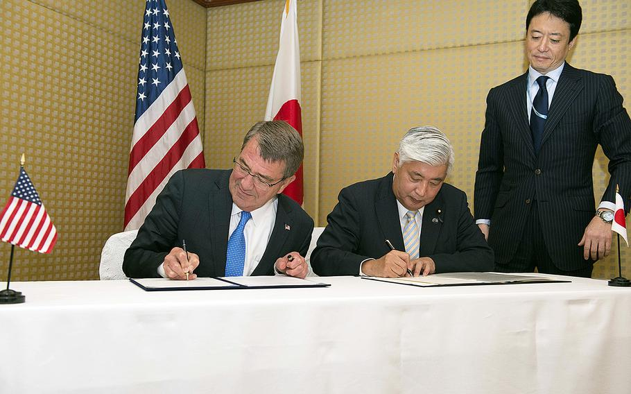 Secretary of Defense Ash Carter signs a reciprocal defense agreement with Japanese Minister of Defense Gen Nakatani in Singapore, June 4, 2016.