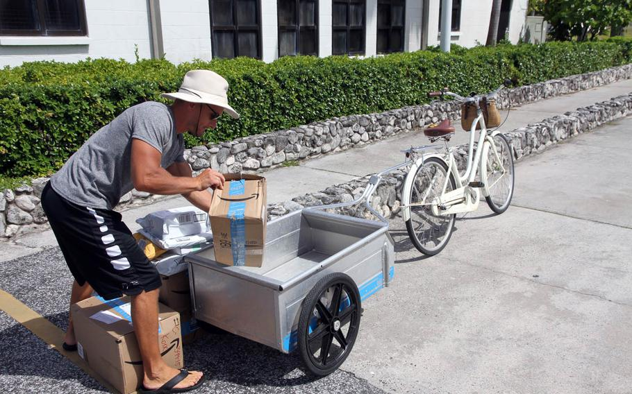 Antti Koski loads up his bike wagon with packages in front of the Kwajalein post office. With few retail stores on the small island, online shopping is a lifeline for residents.