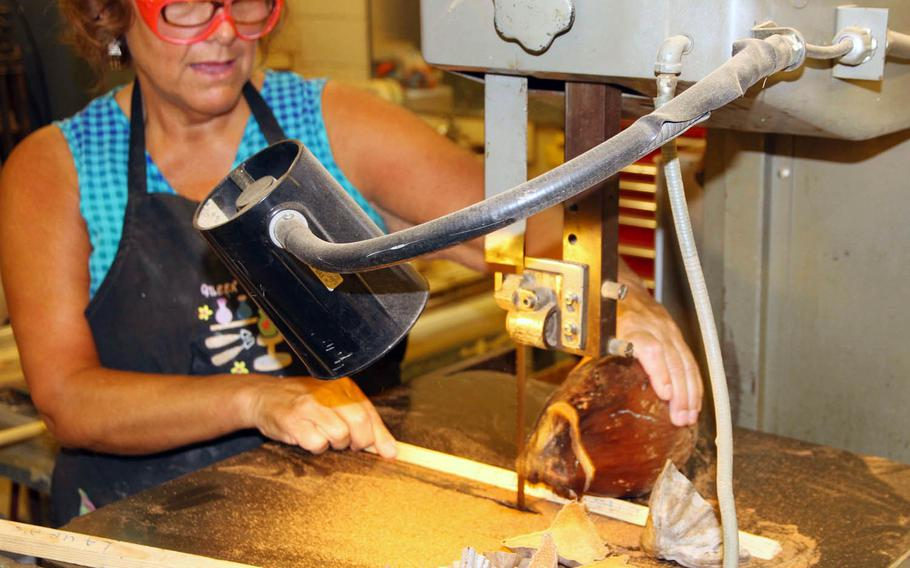"""Laura Alves uses a band saw at the Kwajalein Island hobby center to cut coconuts that she decorates as Christmas """"snow-conut"""" characters. Islanders make the most of materials on hand, including the wooden pallets that carry in supplies."""