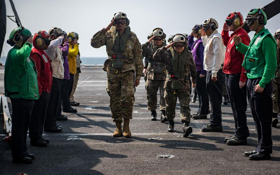 Sideboys from the aircraft carrier USS Carl Vinson salute Gen. Vincent Brooks, center left, U.S. Forces Korea commander, Gen. Lee Sun Jin, center right, chairman of the South Korean Joint Chiefs of Staff, center right, and Gen. Leem Ho-young, deputy commander of the Combined Force, on the flight deck, Sunday, March 12, 2017.