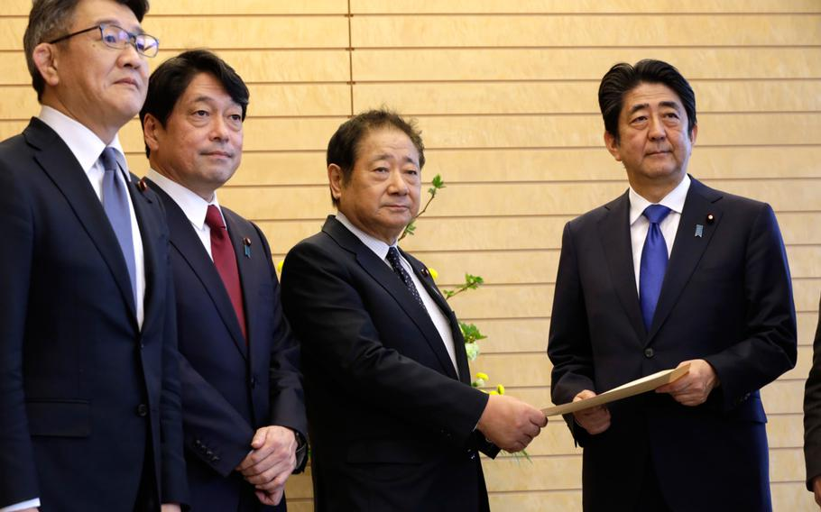 Hiroshi Imazu, second right, Chairman of Research Commission on Security of Japan's ruling Liberal Democratic Party (LDP) submits a proposal on missile defense to Japanese Prime Minister Shinzo Abe, right, flanked by former Defense Minister Itsunori Onodera, second left, head of LDP panel, at the prime minister's office in Tokyo, Thursday, March 30, 2017.