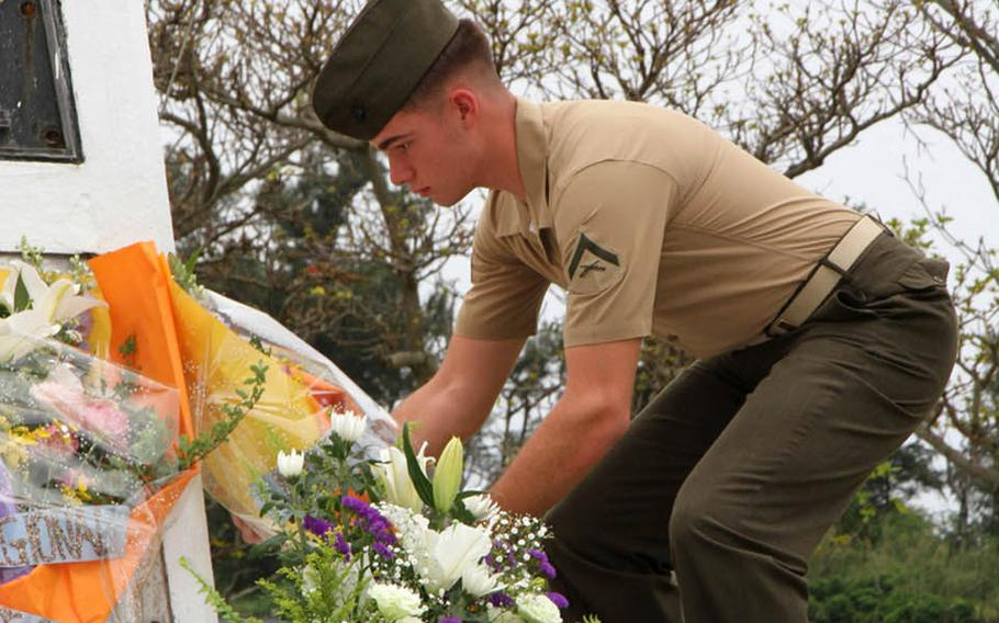 A Marine places flowers at the memorial for acclaimed war correspondent Ernie Pyle, who was killed at this spot on April 18, 1945.