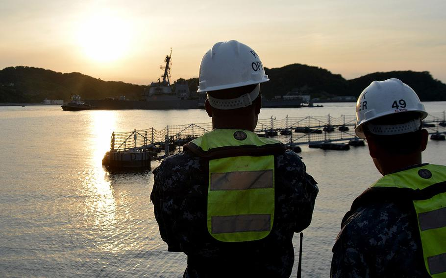 Sailors watch pier-side as the destroyer USS Fitzgerald returns to Fleet Activities Yokosuka on June 17, 2017 after a collision with a merchant vessel while operating southwest of Yokosuka, Japan.