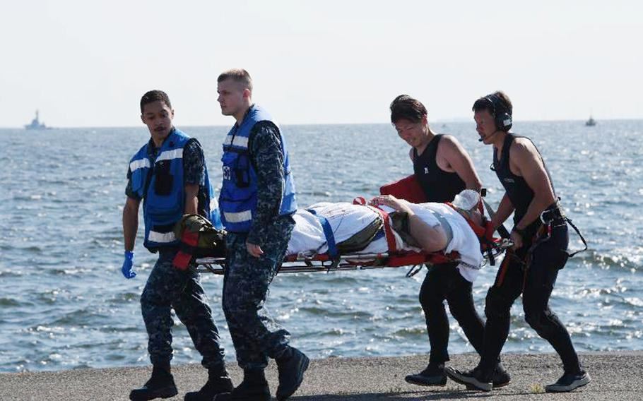 An injured person from the USS Fitzgerald personnel is carried by U.S. and Japanese personnel, at U.S. Naval Base Yokosuka, Japan, on Saturday, June 17, 2017, after the U.S. destroyer collided with a Philippine-registered container ship ACX Crystal.