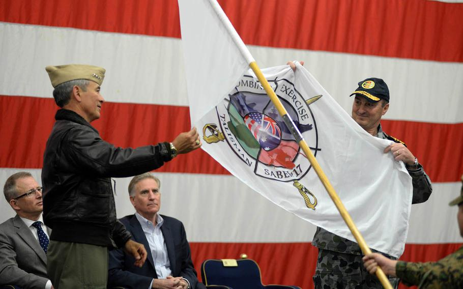 Adm. Harry Harris, left, commander of U.S. Pacific Command, and Royal Australian Navy Vice Adm. David Johnston, Australian Defense Force chief of joint operations, unfurl the Talisman Saber 2017 flag during an opening ceremony aboard the USS Bonhomme Richard, Thursday, June 29, 2017.
