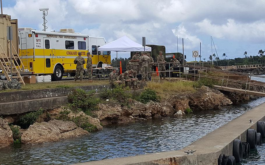 Military personnel gather at the search and rescue command center on Wednesday, Aug. 16, 2017 in Haleiwa, Hawaii. Rescue crews were searching for five soldiers who were aboard an Black Hawk helicopter that crashed several miles off Oahu's North Shore late Tuesday.