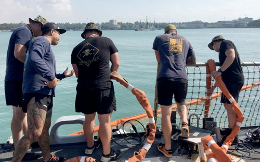 U.S. Navy and Marine Corps divers provide support to the USS John S. McCain at Changi Naval Base, Singapore, Aug. 23, 2017.