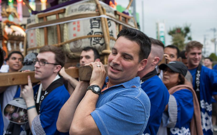 Col. Sergio Vega Jr., 374th Airlift Wing vice commander, carries the wing mikoshi during the 67th Annual Fussa Tanabata Festival at Fussa City, Japan, Aug. 4, 2017. The festival gave Yokota members an opportunity to build friendships with the local community while experiencing Japanese culture.