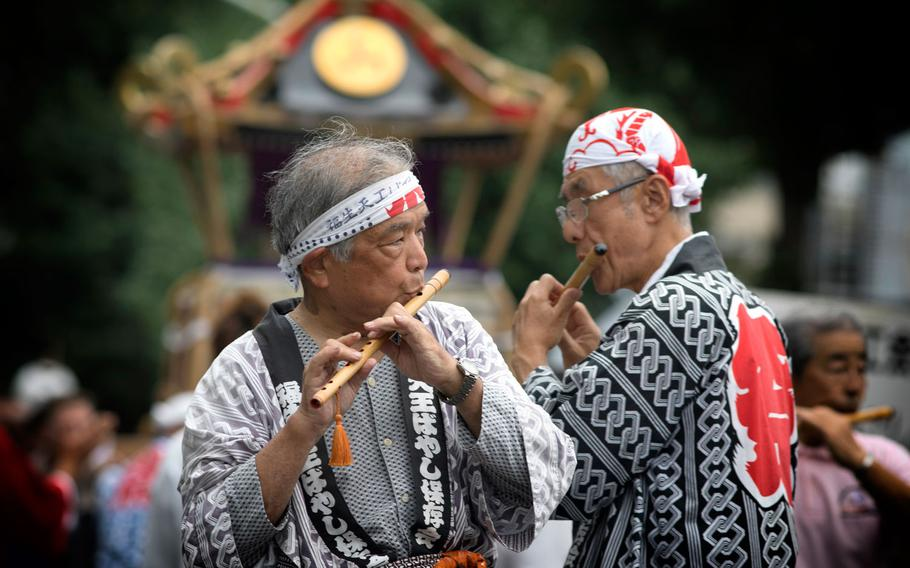 """Members from the Fussa Tennou Hayashi Hozonkai play Japanese flutes during the 67th Annual Fussa Tanabata Festival at Fussa City, Japan, Aug. 4, 2017. A form of Japanese music, called """"hayashi"""" roused the movement of parade floats."""