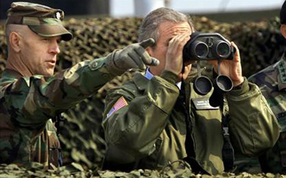 President George W. Bush looks through binoculars at North Korea during a visit to the Demilitarized Zone on Feb. 20, 2002.