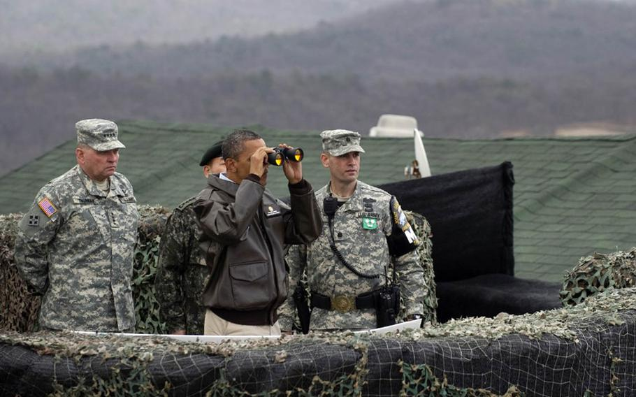 President Barack Obama looks through binoculars at North Korea during a visit to the Demilitarized Zone on March 25, 2012.