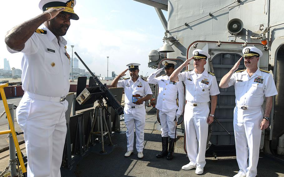 U.S. Navy Rear Admiral Gregory Harris, commander of Carrier Strike Group 11, right, and Capt. Justin A. Kubu, commanding officer of the USS Princeton, middle, salute Commodore Sanjeewa Dias, the director of naval operations Sri Lankan Navy, as he comes aboard the Princeton during a port visit on Saturday, Oct. 28, 2017.