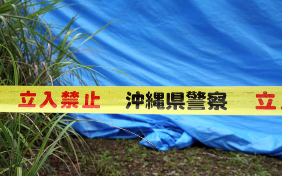 Police tape and a blue tarp mark the site where the body of Rina Shimabukuro was found on Okinawa in 2016.