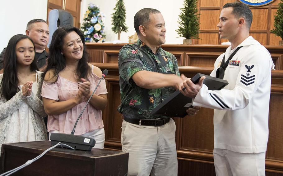 Petty Officer 1st Class Anthony Mugavero, assigned to U.S. Naval Base Guam Harbor Patrol, receives a legislative resolution from Sen. Dennis Rodriguez Jr. at the Guam Congress Building on Friday, Dec. 29, 2017.