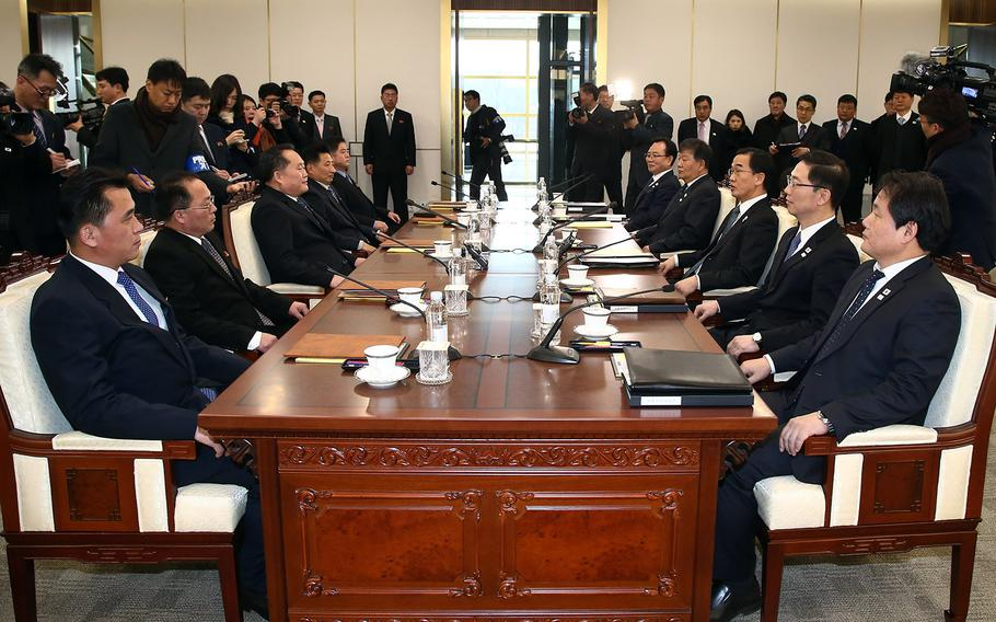 Members of the North Korean delegation, left, sit across from South Korean officials during the first high-level talks between the two countries in more than two years, Tuesday, Jan. 9, 2017. The meeting took place in the truce village of Panmunjom.