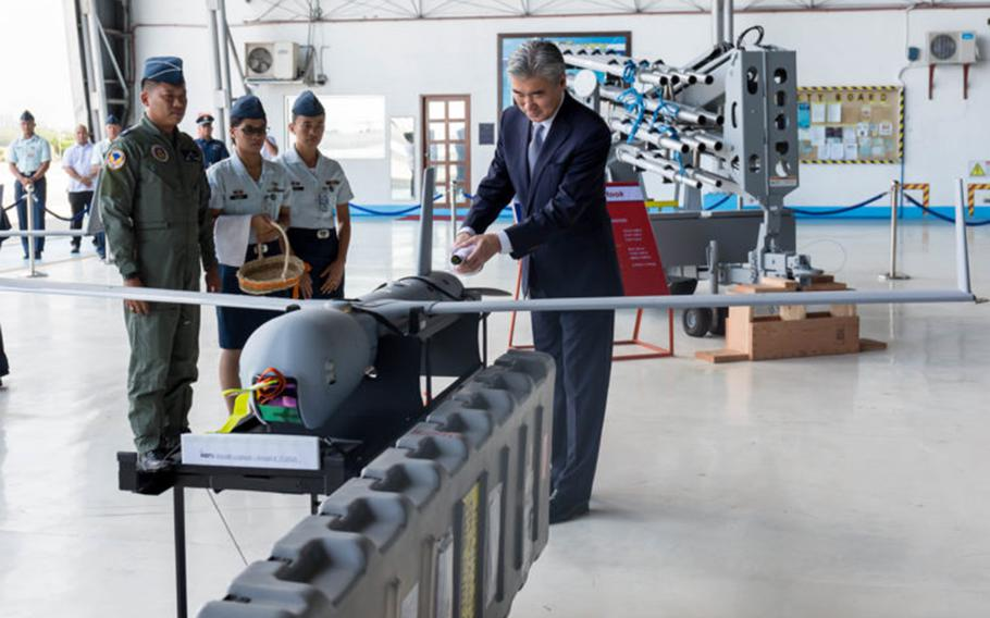 U.S. Ambassador to the Philippines Sung Y. Kim pours champagne over a Scan Eagle Unmanned Aerial Vehicle during a traditional turnover and blessing ceremony on March 13, 2018.