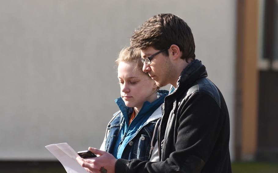 Kaiserslautern High School seniors Madeline MacMillan and Zaccary O'Neil, who organized the walkout at their school, read the names of the 17 victims of the Parkland, Fla., school shooting during a ceremony outside the school on Wednesday, March 14, 2018.