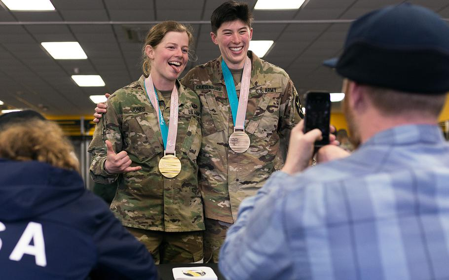 Second Lt. Hannah Jones, 2nd Battalion, 20th Field Artillery Regiment and Sara Cratsenburg pose with Paralympian Noah Elliott's gold and bronze medals as Paralympian Jimmy Sides takes the photo at Camp Casey, South Korea, Saturday, March 17, 2018.