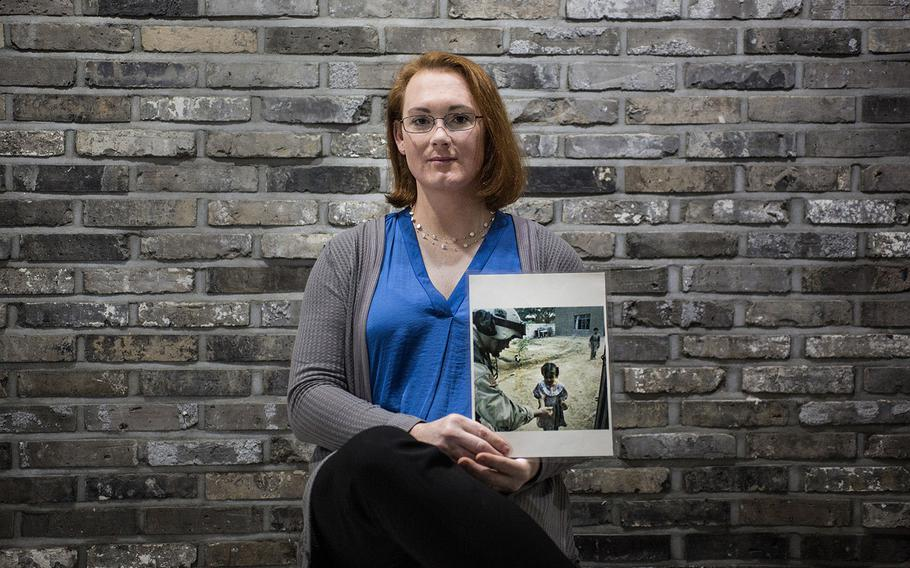Chief Warrant Officer 3 Lindsey Muller poses for a photo while holding an image from her tour to Iraq on Thursday, March 29, 2018.