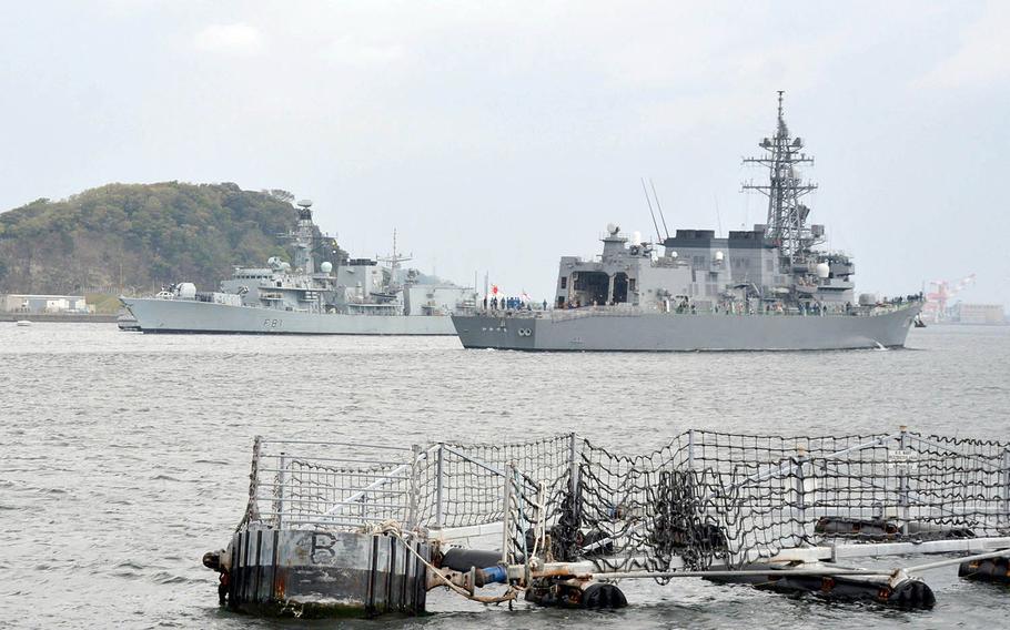 The British Royal Navy frigate HMS Sutherland, left, passes the Japanese destroyer JS Ikazuchi as it arrives at Yokosuka Naval Base, Japan, Wednesday, April 11, 2018.