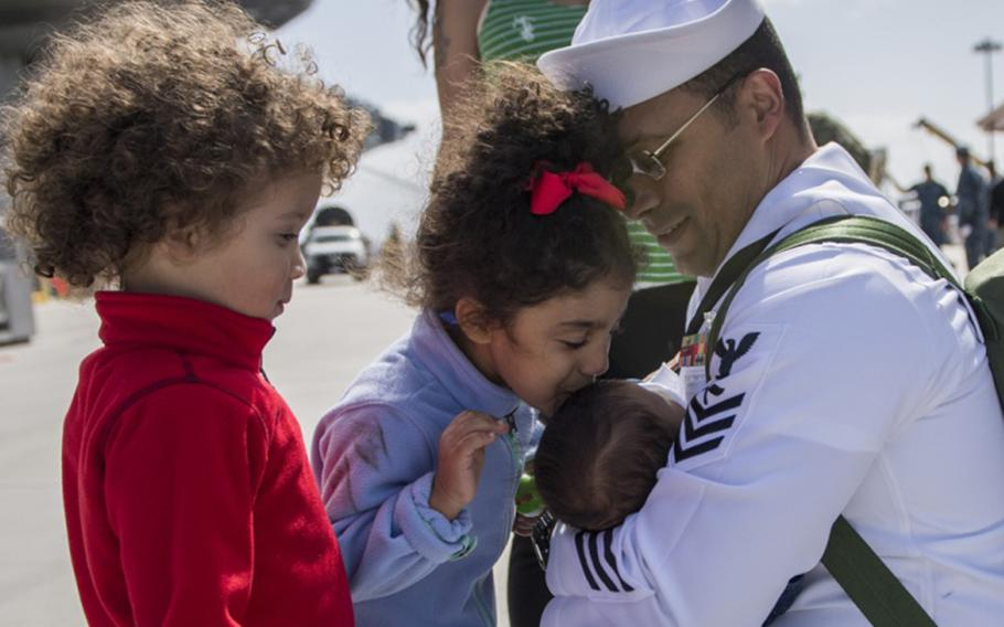 The family of Petty Officer 1st Class Class Willy Cruceta, assigned to Nimitz-class aircraft carrier USS Carl Vinson, introduces him to his newborn baby at the ship's homecoming ceremony in San Diego on April 12, 2018.