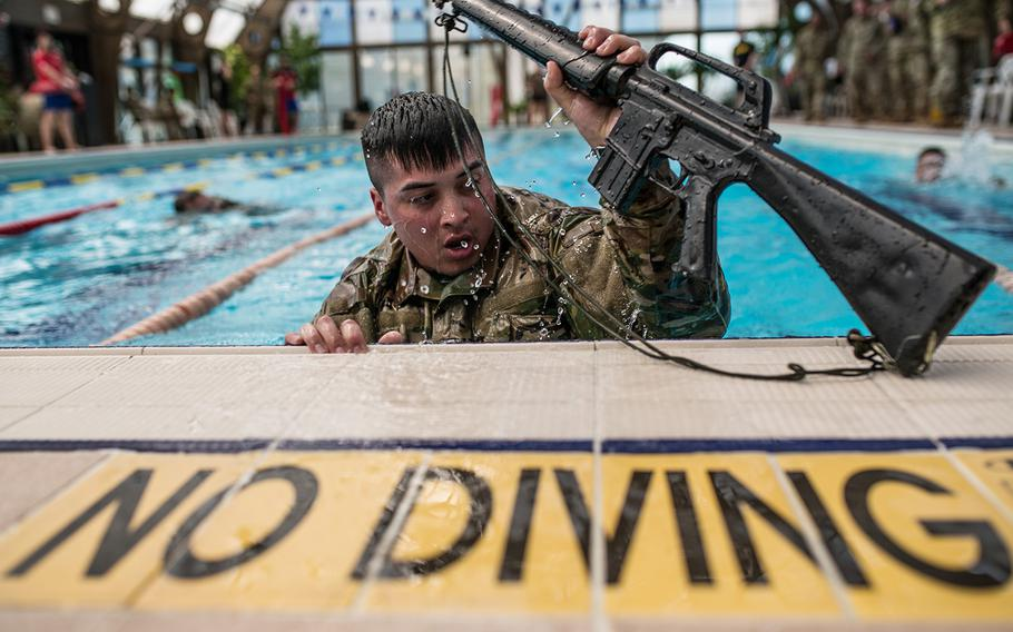 Spc. Cristepher Colon grabs a rifle during the 2nd Infantry Division's Best Warrior competition at Camp Hovey, South Korea, Wednesday, April 11, 2018.