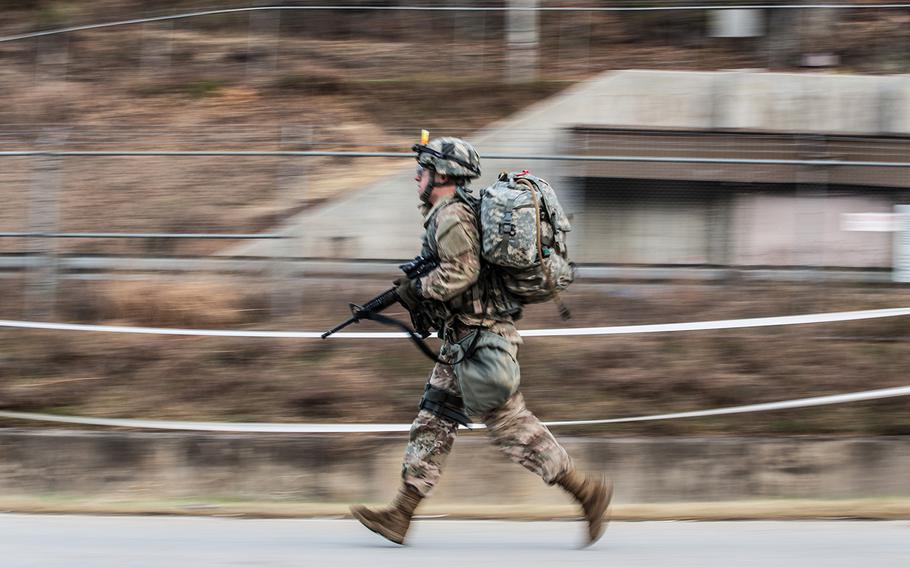A soldier races from the turn-around point during a 12-mile road march as part of the 2nd Infantry Division's Best Warrior competition at Camp Casey, South Korea, Thursday, April 12, 2018.