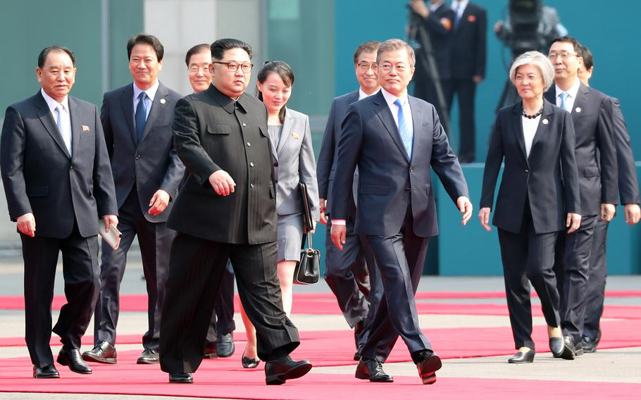 North Korean leader Kim Jong Un and South Korean President Moon Jae-in are flaked by aides and other political leaders including Kim's sister Kim Yo Jong, center, on Friday, April 27, 2018.