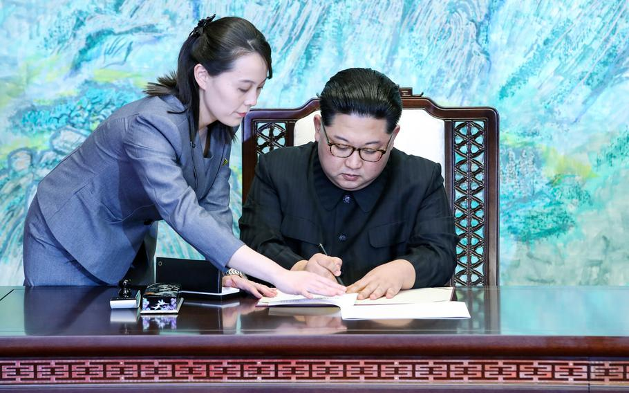 North Korean leader Kim Jong Un, joined by his younger sister, Kim Yo Jong, signs the Panmunjom Declaration during the Inter-Korean Summit on Friday, April 27, 2018.