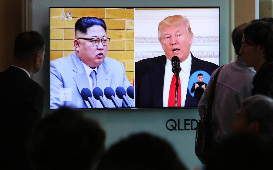 People watch a TV screen showing file footage of U.S. President Donald Trump, right, and North Korean leader Kim Jong Un during a news program at the Seoul Railway Station in Seoul, South Korea, on April 21, 2018.