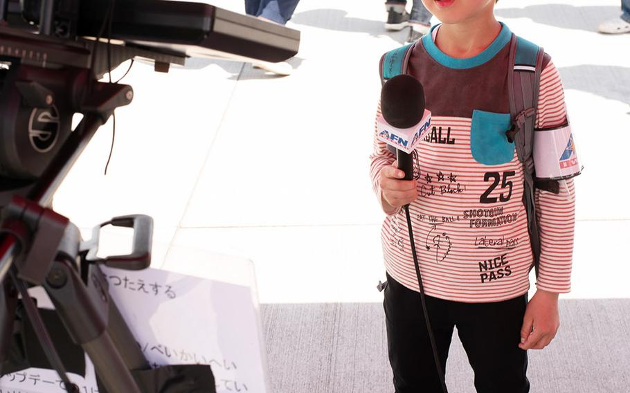 A boy portrays an American Forces Network reporter during the 42nd annual Friendship Day at Marine Corps Air Station Iwakuni, Japan, Saturday, May 5, 2018.