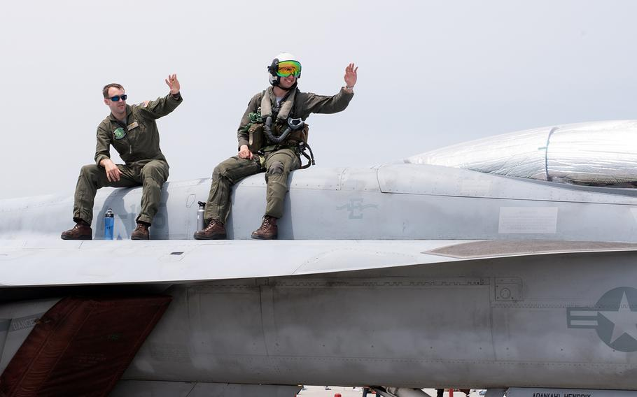 Navy pilots pose atop an F/A 18E Super Hornet during the 42nd annual Friendship Day at Marine Corps Air Station Iwakuni, Japan, Saturday, May 5, 2018.