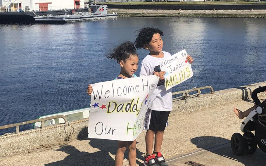 Kianna Brown, 5, and Tavion Brown, 7, await their father's arrival at Yokosuka Naval Base, Japan, Tuesday, May 22, 2018. Their father, Chief Petty Officer Kevin Brown, serves aboard the USS Milius, which is the latest ship to join the Navy's 7th Fleet.