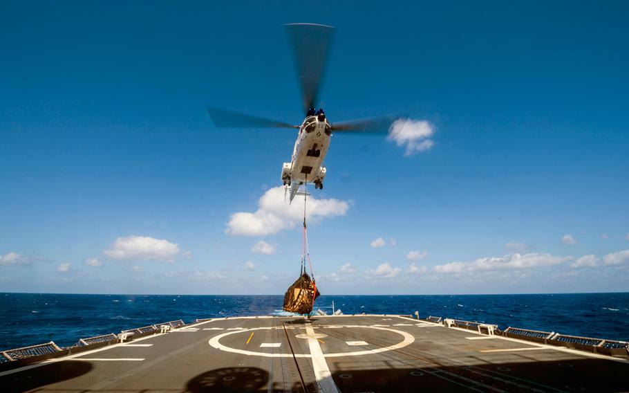 An SA-330J Puma helicopter, assigned to the Lewis and Clark-class dry cargo ship USNS Wally Schirra (T-AKE 8), takes off with cargo from the flight deck of the Ticonderoga-class guided-missile cruiser USS Antietam (CG 54) during a vertical replenishment in the Philippine Sea in March 2018.