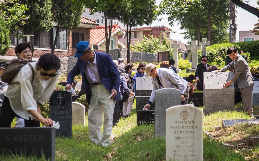 South Koreans clean U.S. grave sites at Yanghwajin Cemetery in Seoul, South Korea, Monday, May 28, 2018.