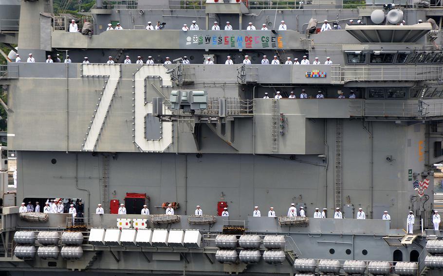 Sailors man the rails of the aircraft carrier USS Ronald Reagan (CVN 76) as it departs U.S. Fleet Activities Yokosuka on May 29, 2018.